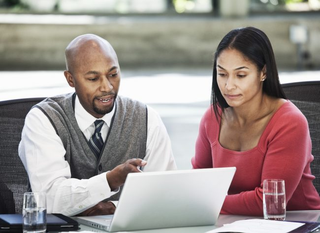 Black business man and mixed race caucasian woman in a business center meeting.